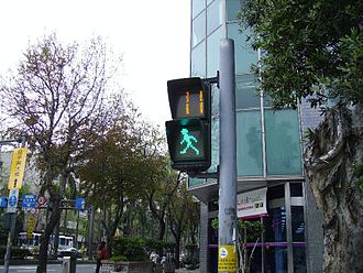 "Traffic light control and coordination - Pedestrian traffic signal in Taiwan, featuring a ""Walking green man"" below a countdown display where the ""Red Man"" once stood."