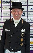 Das Foto zeigt das Gesicht des Dressurreiter Hubertus Schmidt. Er trägt einen schwarzen Zylinder und einen schwarzen Frack.