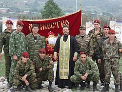 Soldiers and a priest in front of a banner