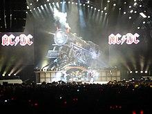 Quatre membre de groupe sur scne devant un public avec une locomotive factice et deux logos ACDC en fond