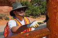 A maintenance worker stains a fence at Arches (8043876198).jpg