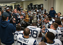 A man speaks to American football players in uniform in a locker room in front of a large trophy.