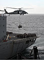 An MH-60 Seahawk helicopter transfers supplies from the fleet replenishment oiler USNS Rappahannock (T-AO 204) to the amphibious assault ship USS Boxer (LHD 4) during an under way replenishment in the Pacific 110317-N-ZS026-044.jpg