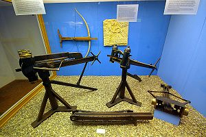 History of crossbows - Arsenal of ancient mechanical artillery: Catapults (standing), chain drive of Polybolos (bottom center), Gastraphetes (on wall)