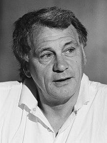 Photographie en noir et blanc. Portrait de Bobby Robson en chemise blanche, regardant vers sa gauche.