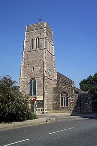 A tall flint tower with the body of the church extending beyond it