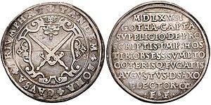 Zwei runde Silbermünzen nebeneinander, die linke zeigt ein großes Wappen mit zwei Schwertern, die rechte acht Zeilen Schrift auf der ganzen Fläche