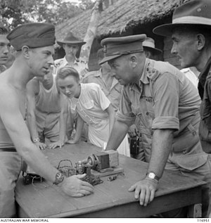 Tom Eastick - Eastick (second right) views a homemade radio constructed by prisoners at the Batu Lintang POW/internment camp