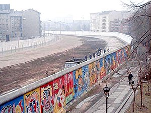 "Berlin Wall - View from the West Berlin side of graffiti art on the Wall in 1986. The Wall's ""death strip"", on the east side of the Wall, here follows the curve of the Luisenstadt Canal (filled in 1932)."
