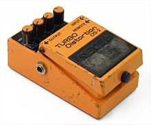 A small effect unit pedal, painted in orange paint that is scuffed from heavy use.