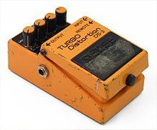 Um pequeno pedal unidade de efeito, pintado em tinta laranja que está raspada do uso pesado.