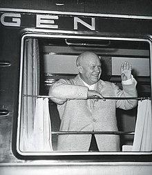 Foto av en smilende mann som vinker fra et skinnevognvindu