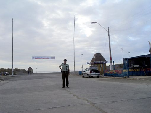 A police officer preventing people from accessing Pichilemu's closest street to the beach, the Costanera. Image: Diego Grez.