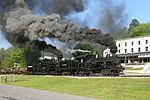 A locomotive on railroad tracks billowing black smoke.