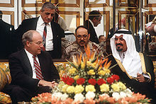 A balding man with glasses, wearing a suit, sits on the left of a couch next to a hirsute man in traditional Arab headress and attire on the right. In front, on a coffee table, is a vase full of flowers; behind them is a man in desert camouflage and another man in a suit in front of a mirrored partition