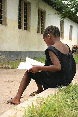 Child in Tanzania reading a book. Original cap...