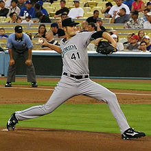 "A man in a grey baseball uniform with ""FLORIDA 41"" on the chest and a black baseball glove on his left hand pitching a baseball right-handed."
