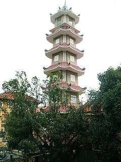 A bell tower that has seven levels of the same pattern, is octagonal with alternating long and short sides, has ornate tiling, and is surrounded by plants.