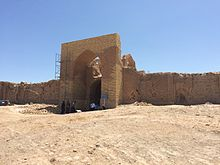 Main gate of the 11th-century Dayahatyn caravansaray in Lebap velayat, Turkmenistan. The gate is made of adobe bricks and sits in a dry, sandy area.