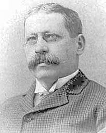 A black and white photograph of the head and shoulders of a man with a mustache and glasses