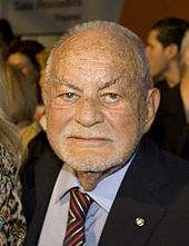 A squarish faced man in a suit and tie: he is balding with closely cropped white hair, and sports a stubble of white beard.