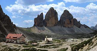 Blick auf die Nordwände der Drei Zinnen. Links im Vordergrund die Dreizinnenhütte und eine Kapelle.