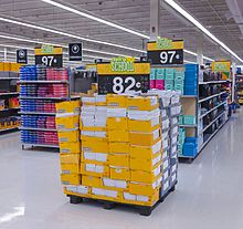 "Several people shopping in an area with high shelves on the right stacked with spiral notebooks and other stationery products in open yellow boxes. At the top of the shelves are several blue signs with a small stylized starburst logo in yellow and ""Everyday Low Price"" in white text, on a red background. Strip fluorescent lights on the ceiling illuminate the scene; a yellow sign hanging from the ceiling has an octagon with ""back to school"" and text in English and Spanish beneath it. On the left are shelves reaching camera height; a sign in the front bottom says ""$9.97""."