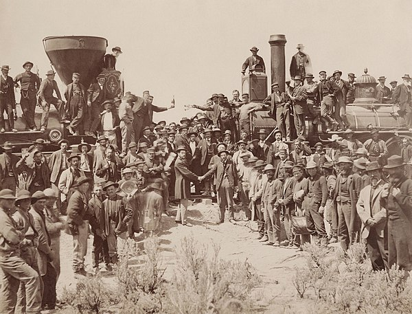 The completion of the Transcontinental Railroad (1869) at First Transcontinental Railroad, by Andrew J. Russell. East and West Shaking hands at the laying of last rail Union Pacific Railroad - Restoration.jpg