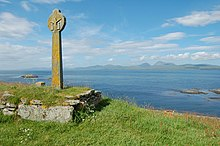 A stone cross in the Celtic style sits in a grassy field on an overgrown stone plinth. Small rocky reefs lie in the sea beyond, and there are high green hills in the distance.