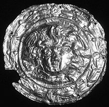 Black and white photograph of a circular gold disc with Medusa's head and hair in the centre