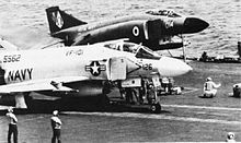 Two jet aeroplanes on catapults awaiting launch from an aircraft carrier