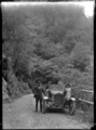 Four people with a car on the Akatarawa Road, 1923 ATLIB 299515.png