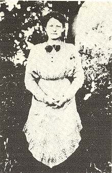 Young woman wearing an apron and facing forwards