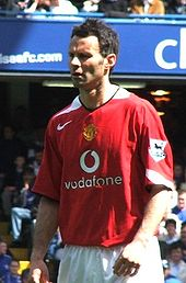 A photograph of a man with dark hair and a focused expression on his face, wearing a red shirt and white shorts.