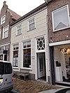foto van Huis met gebosseerd witgepleisterde lijstgevel, kroonlijst op klossen en schilddak