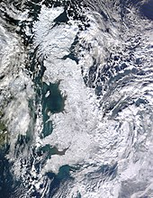 A satellite photo of Great Britain and Ireland. Great Britain is white as a result of snow cover and Ireland is mostly green with some snow cover in the east. Cloud is scatted across the surrounding sea and eastern Ireland, as well as the east coast of Great Britain (especially the southeast).