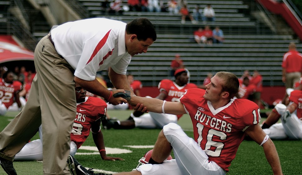 Potograph of Schiano interacting with a player during pre-game warmups