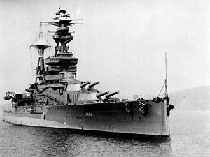 A three-quarter view of a heavily-armoured battleship at anchor. There are two main turrets visible before the bridge, each housing a pair of 15-inch guns. 6-inch guns are housed in a row of individual sideways-facing sponsons. The flank of the ship has a conspicuous bulge at the waterline.