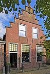 foto van Tot pakhuis gewijzigd woonhuis met zolder- en vlieringluik onder zadeldak tegen trapgevel met toppilaster