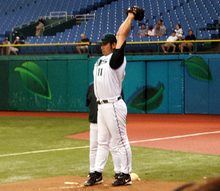 A Japanese man wearing a Devil Ray baseball uniform points his arms upward as he prepares to pitch in the bullpen.