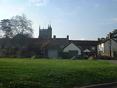 Church tower seen arising behind stone buildings with tile roofs, one of which has a pub sign. Foreground is grass