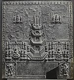Relief with a pagoda in the centre surrounded by various images of deities. The lower part of the plaque bears an inscription which is framed by two deities.