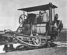 A machine very similar in arrangement to the Holt seventy-five tractor, but with a steam boiler where later models would have the internal combustion engine fitted. A prominent chain drive extends the length of the vehicle from the steam engine to the rear, tracked wheels.