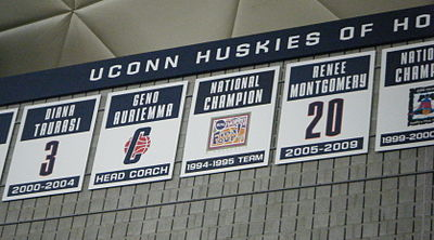 Gray stone wall with five placards attached in a row, with numbers or logos on them. Above is a triangular-grid ceiling.