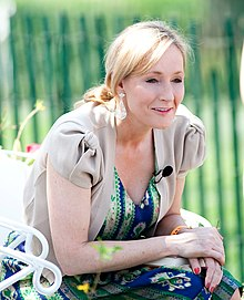 J. K. Rowling, author of Harry Potter and the Half-Blood Prince, crouches. She is wearing a blue dress under a grey jacket.
