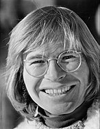 A man with long blond hair and glasses, smiling broadly