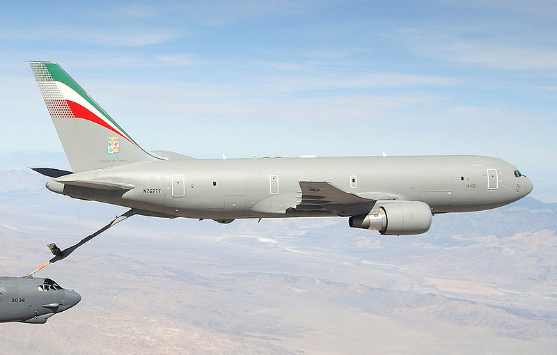 A mostly-gray KC-767, with refueling probe extended, transferring fuel to a B-52 in the left-bottom hand corner.