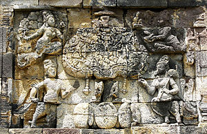 Kalpavriksha - Kalpataru, the divine tree of life being guarded by mythical creatures Kinnara and Kinnari, flying Apsara and Devata. 8th century Pawon temple, Java, Indonesia.