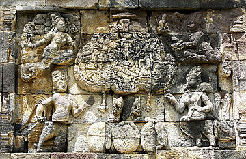 The divine Kalpavriksha tree in mythology, a stone carving of a tree with mythical characters surrounding it.