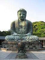 Front view of an outside cross-legged seated statue. The eyes are closed and the hands rest on the lap with palms facing upward. The statue is left-right symmetric, appears green of copper rust and is placed on a stone platform.